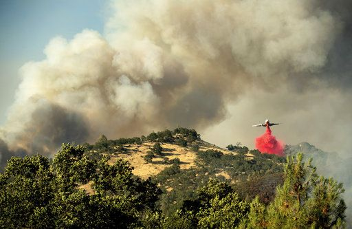 An air tanker drops retardant on a wildfire above the Spring Lakes community on Sunday, June 24, 2018., near Clearlake Oaks, Calif. Wind-driven wildfires destroyed buildings and threatened hundreds of others Sunday as they raced across dry brush in rural Northern California.