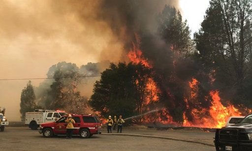 In this photo provided by the Cal Fire Communications, firefighters battle a wildfire in an area northeast of Clearlake Oaks, Calif., Sunday, June 24, 2018 Wind-driven wildfires destroyed buildings and threatened hundreds of others Sunday as they raced across dry brush in rural Northern California. (Jonathan Cox/Cal Fire Communications via AP)