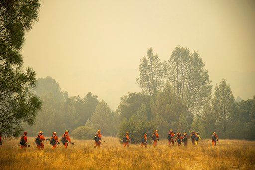 An inmate crew battles a wildfire in Spring Valley, Calif., Sunday, June 24, 2018. Wind-driven wildfires destroyed buildings and threatened hundreds of others Sunday as they raced across dry brush in rural Northern California. (Paul Kitagaki Jr./The Sacramento Bee via AP)