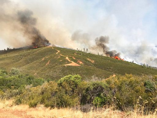 In this photo provided by the California Department of Forestry and Fire Protection, the Pawnee Fire wildfire burns northeast of Clearlake Oaks, Calif., early Sunday, June 24, 2018. The Pawnee Fire, which broke out Saturday, was one of four wildfires burning in largely rural areas as wind and heat gripped a swath of California from San Jose to the Oregon border. (Jonathan Cox/California Department of Forestry and Fire Protection via AP)