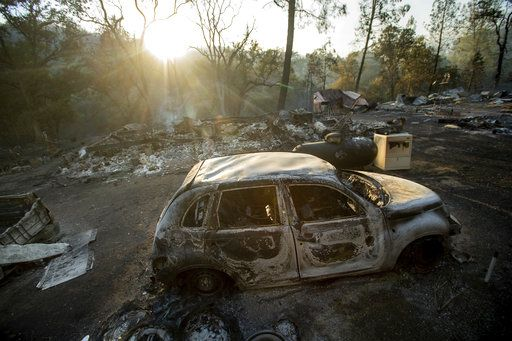 A vehicle scorched by a wildfire rests in a clearing on Wolf Creek Road near Clearlake Oaks, Calif., Sunday, June 24, 2018. Wind-driven wildfires destroyed buildings and threatened hundreds of others Sunday as they raced across dry brush in rural Northern California.
