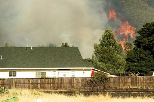 Flames from a wildfire rise above the Spring Lakes community on Sunday, June 24, 2018, near Clearlake Oaks, Calif. Wind-driven wildfires destroyed buildings and threatened hundreds of others Sunday as they raced across dry brush in rural Northern California.