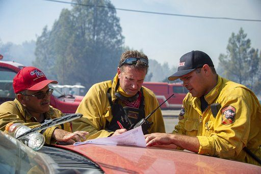 A Cal Fire incident management team discusses the plan to battle a wildfire in Spring Valley, Calif., Sunday, June 24, 2018. Wind-driven wildfires destroyed buildings and threatened hundreds of others Sunday as they raced across dry brush in rural Northern California. (Paul Kitagaki Jr./The Sacramento Bee via AP)