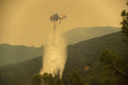 Cal Fire helicopter helps battle a wildfire in Spring Valley, Calif., Sunday, June 24, 2018. Wind-driven wildfires destroyed buildings and threatened hundreds of others Sunday as they raced across dry brush in rural Northern California. (Paul Kitagaki Jr./The Sacramento Bee via AP)