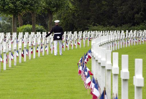 FILE - In this May 27, 2018, file photo, U.S. Marine Corps Sergeant Major Darrell Carver, based in North Carolina, touches a headstone at the Aisne-Marne American Cemetery in Belleau, France. France and Belgium are urging UNESCO to designate scores of their World War I memorials and cemeteries as World Heritage sites as the centennial remembrance of the 1914-1918 war nears its end. (AP Photo/Virginia Mayo, File)