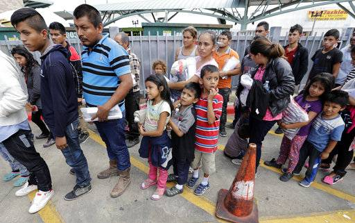 In this Thursday, June 23, 2018 photo, migrant families rest from their travels to Matamoros, Mexico, along Gateway International Bridge which connects to Brownsville, Texas, as they seek asylum in the United States. (Miguel Roberts/The Brownsville Herald via AP)