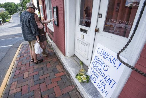 "Passersby examine the menu at the Red Hen Restaurant Saturday, June 23, 2018, in Lexington, Va. White House press secretary Sarah Huckabee Sanders said Saturday in a tweet that she was booted from the Virginia restaurant because she works for President Donald Trump. Sanders said she was told by the owner of The Red Hen that she had to ""leave because I work for @POTUS and I politely left."""