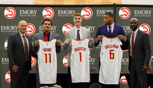 Atlanta Hawks NBA basketball team first-round draft picks, Trae Young (11), Kevin Huerter (1) and Omari Spellman (6) poses with general manager Travis Shlenk, left, and head coach Lloyd Pierce during a news conference Monday, June 25, 2018, in Atlanta.