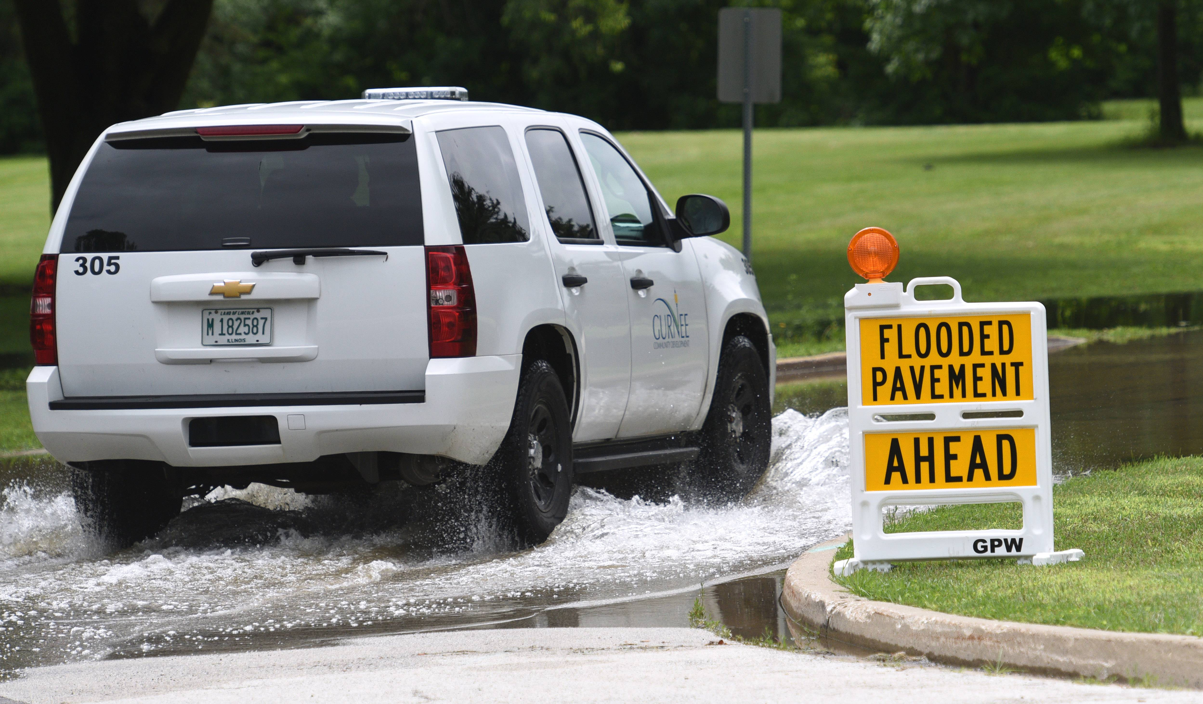 Emerald Avenue is passable as rising Des Plaines River waters cover the road at Kilbourne Road Wednesday morning in Gurnee.