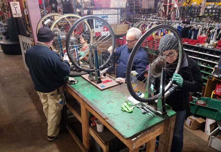 "Volunteers learning to ""true"" (straighten) wheels at Working Bikes in Chicago."