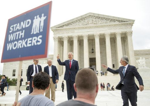CORRECTS LEFT TO RIGHT - Illinois Gov. Bruce Rauner gives a thumbs up outside the Supreme Court, Wednesday, June 27, 2018 in Washington. From left are, Liberty Justice Center's Director of Litigation Jacob Huebert, plaintiff Mark Janus, Rauner, and Liberty Justice Center founder and chairman John Tillman.  The Supreme Court ruled Wednesday that government workers can't be forced to contribute to labor unions that represent them in collective bargaining, dealing a serious financial blow to organized labor.
