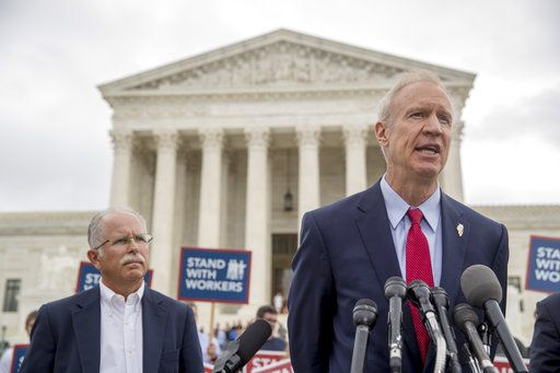 Illinois Gov. Bruce Rauner, right, accompanied by plaintiff Mark Janus, left, speaks outside the Supreme Court after the court rules in a setback for organized labor that states can't force government workers to pay union fees, Wednesday, June 27, 2018, in Washington.