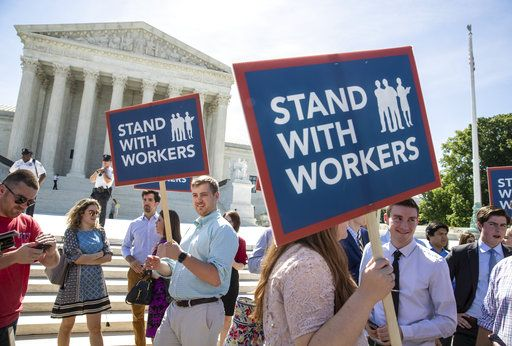 In this Monday, June 25, 2018 photo, people gather at the Supreme Court awaiting a decision in an Illinois union dues case, Janus vs. AFSCME, in Washington.  The Supreme Court says government workers can't be forced to contribute to labor unions that represent them in collective bargaining, dealing a serious financial blow to organized labor.