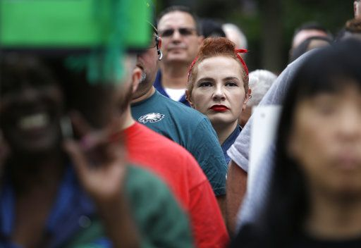 Amanda Hammock, center, a Delaware County, Pa., Democratic party activist, is dressed as Rosie the Riveter as she attends a protest by Philadelphia Council AFL-CIO, Wednesday June 27, 2018, in Philadelphia. The protesters denounced Wednesday's U.S. Supreme Court ruling that government workers can't be forced to contribute to labor unions that represent them in collective bargaining, dealing a serious financial blow to organized labor.
