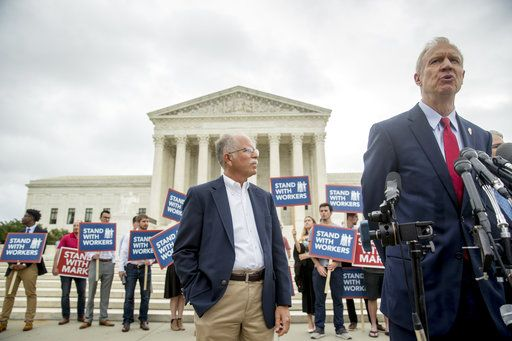 Illinois Gov. Bruce Rauner, right, accompanied by plaintiff Mark Janus, center, speaks outside the Supreme Court after the court rules in a setback for organized labor that states can't force government workers to pay union fees, Wednesday, June 27, 2018, in Washington.