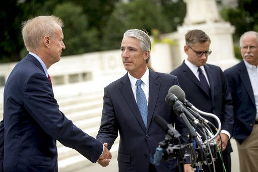 Illinois Gov. Bruce Rauner, left, shakes hands with Liberty Justice Center founder and chairman John Tillman, second from left, as he walks to microphones to speak outside the Supreme Court after the court rules in a setback for organized labor that states can't force government workers to pay union fees, Wednesday, June 27, 2018, in Washington. Also pictured is Liberty Justice Center's Director of Litigation Jacob Huebert, second from right, and plaintiff Mark Janus, right.