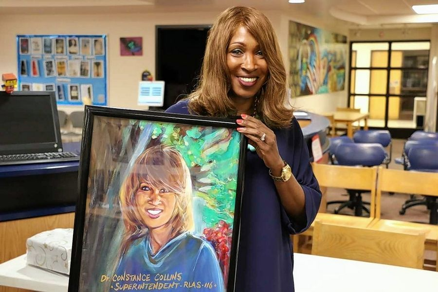 Round Lake Area School District 116 Superintendent Constance Collins poses with a portrait made by Round Lake High School custodian Terry Cagle. The portrait was a gift from the school board.