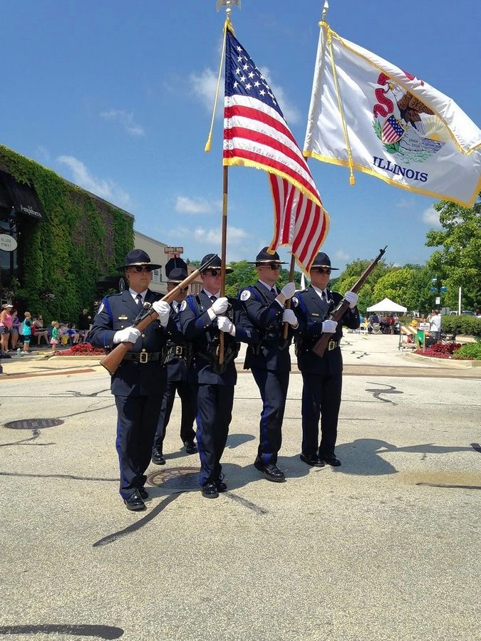 Part of the Palatine Police Department color guard turns the corner at Slade and Brockway streets downtown before firing a salute at the Palatine Hometown Fest parade Saturday.