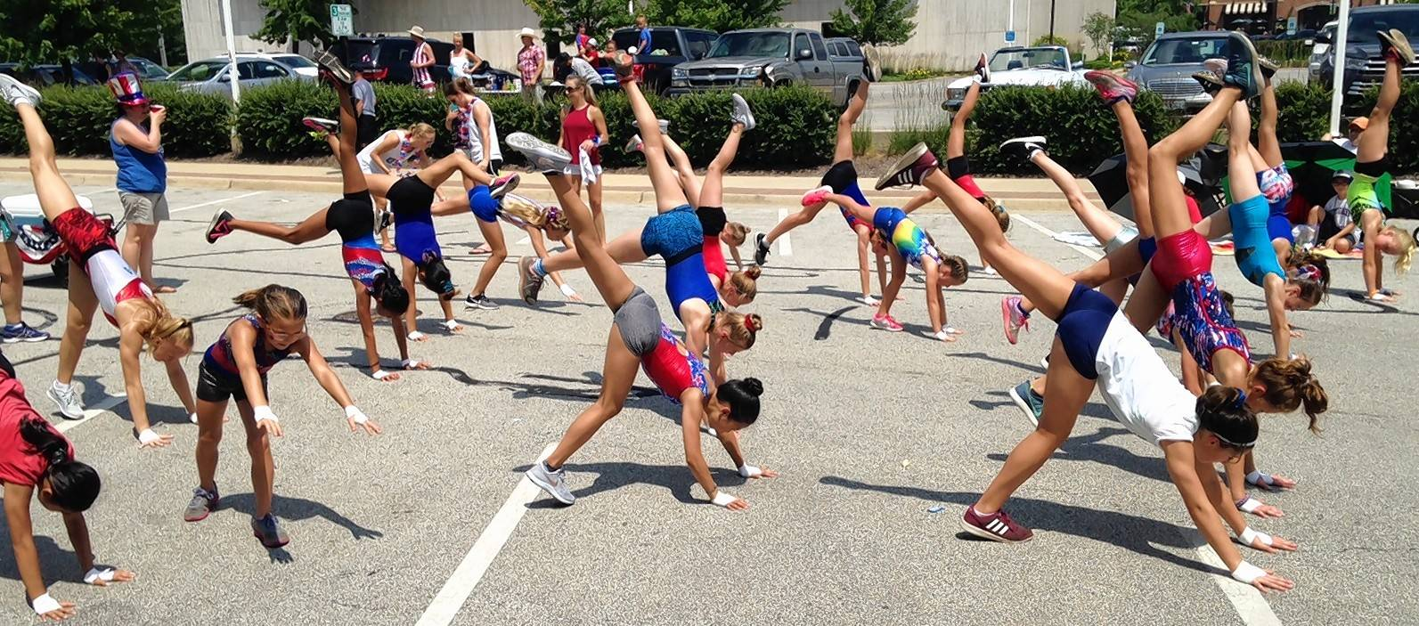 Girls in the Palatine Gymnastics Club do handstands on the hot asphalt during the Palatine Hometown Fest parade Saturday. They also were throwing out handfuls of candy to bystanders.
