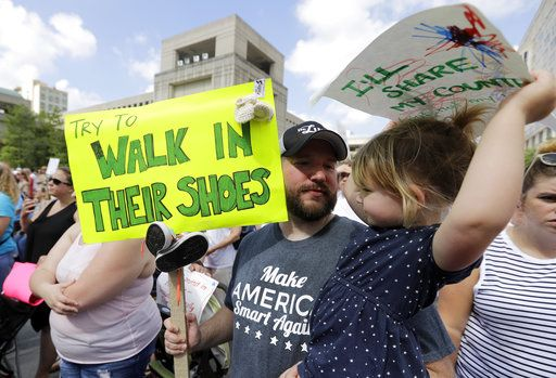 Scott Burns, holds his daughter, Annelle, listen to speakers during a protest of the Trump administration's approach to illegal border crossings and separation of children from immigrant parents at the Statehouse, Saturday, June 30, 2018, in Indianapolis.