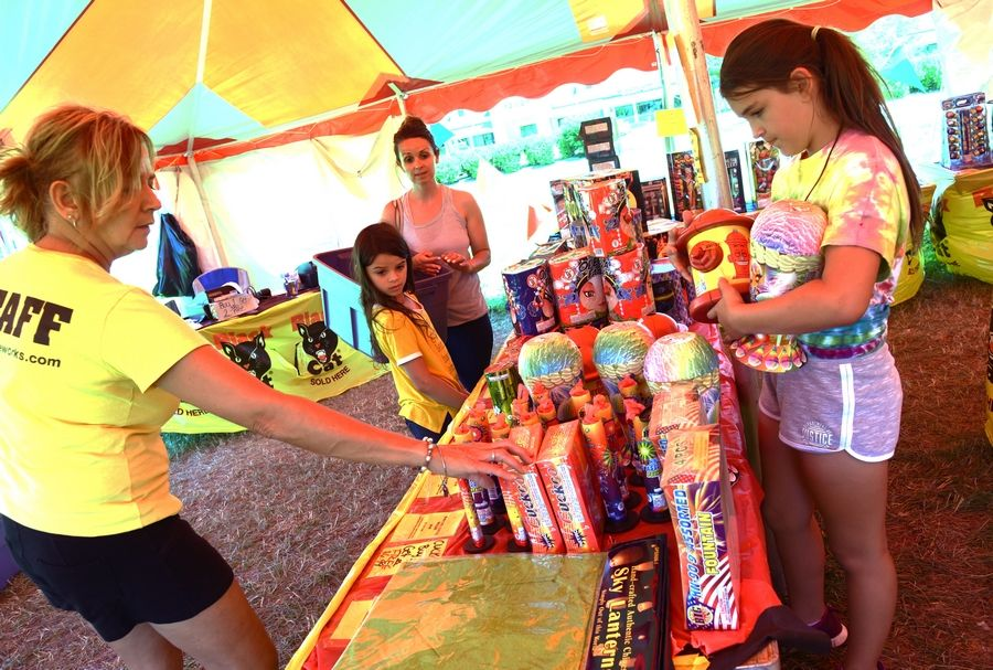 Mickey Kenney, left, with Black Bull Fireworks in Salem Lakes, Wisconsin, explains various fireworks to Antioch resident, Marlen Thompson and her daughters, Cayleigh and Mycah, right. Marlen's family uses the fireworks to celebrate the Fourth of July at a family member's house in Wisconsin.