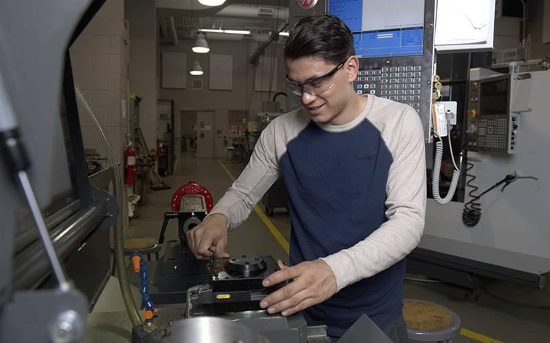 A student uses manufacturing equipment at Elgin Community College's shop facilities. The college is launching two apprenticeship programs this fall in industrial maintenance and nursing assistance.