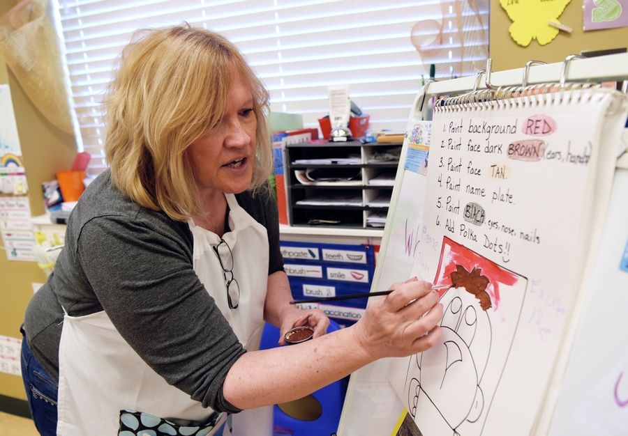 Joni Downey of Johnsburg, who has created a nonprofit program called Characters of Character, shows students how to paint Manners Monkey during a visit to Kiddie Academy in Arlington Heights.