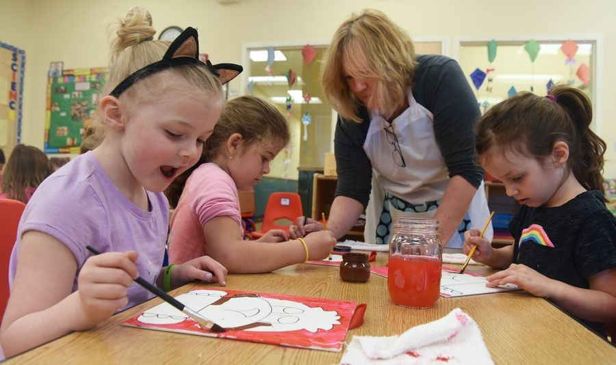"Ella Dimck, 5, left, Iva Dimitrova, 6, and Lauren Cronin paint ""Manners Monkey"" at Kiddie Academy in Arlington Heights. Joni Downey of Johnsburg, second from right, is the creator of a nonprofit program called Characters of Character."