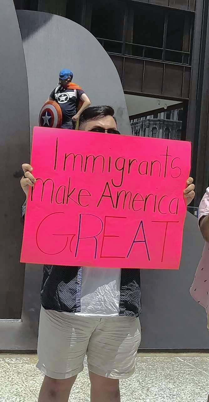 In the shadow of a man dressed as Captain America, this sign speaks to the value of immigrants.