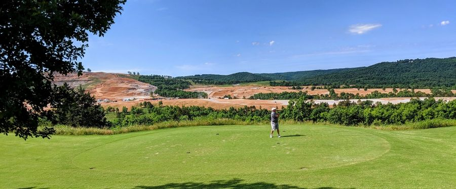 Work progresses at the Payne's Valley course designed by Tiger Woods (background) while golfers play at Buffalo Ridge Springs.