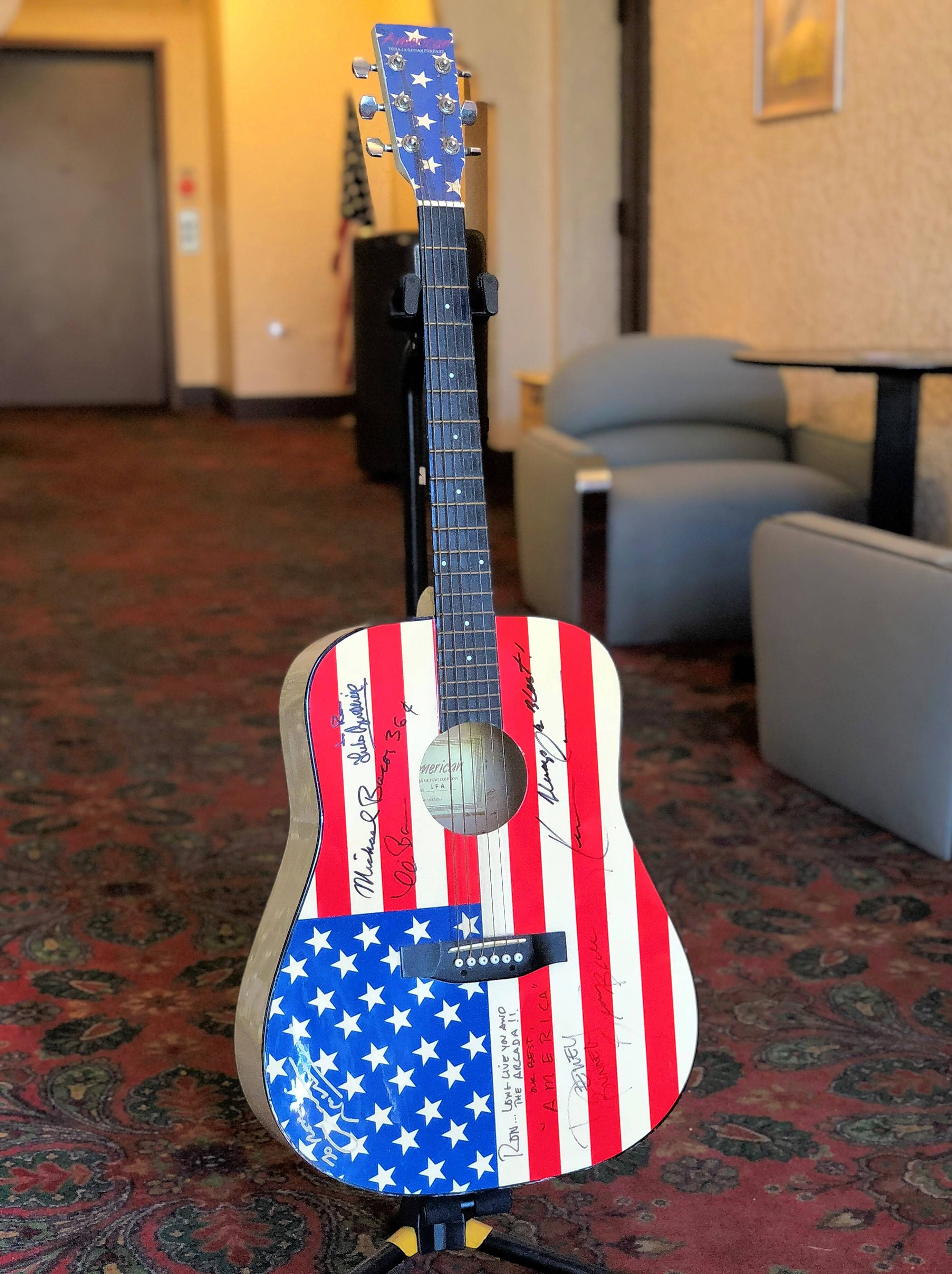 "This six-string, acoustic guitar from the 1970s has sat in Ron Onesti's office for years. recently, he has been asking artists who represent ""America"" to sign it."