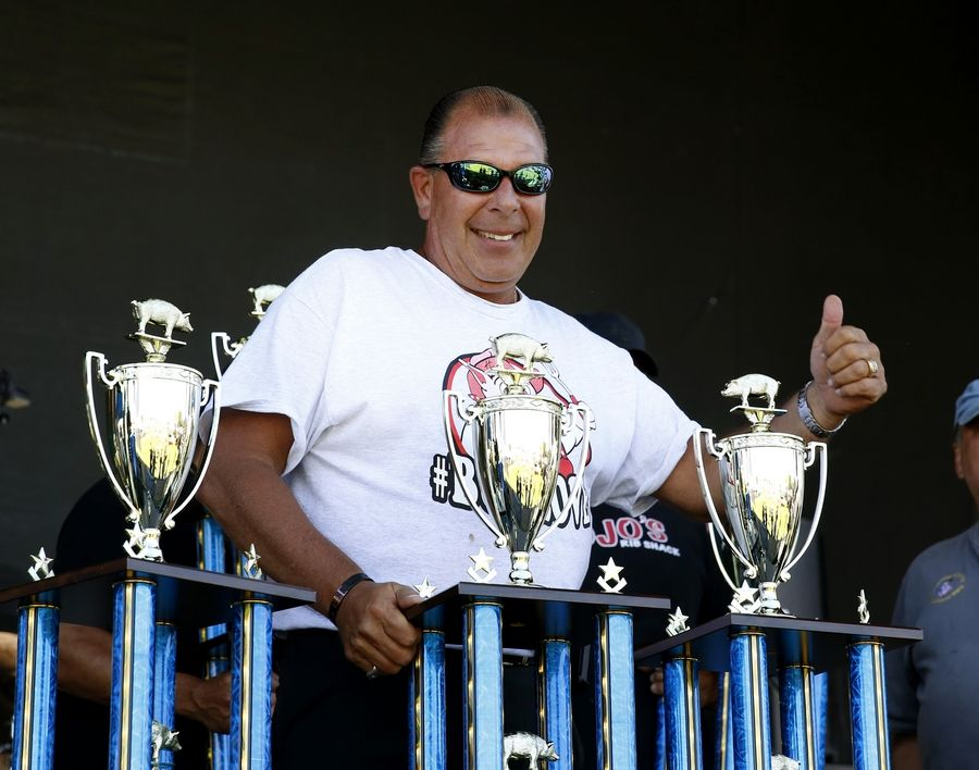 Mark Link of Uncle Bub's BBQ in Westmont stands behind his three winning first place trophies -- Best Ribs, Best Sauce and Kids Choice -- on Friday during the 31st annual Ribfest in Naperville.