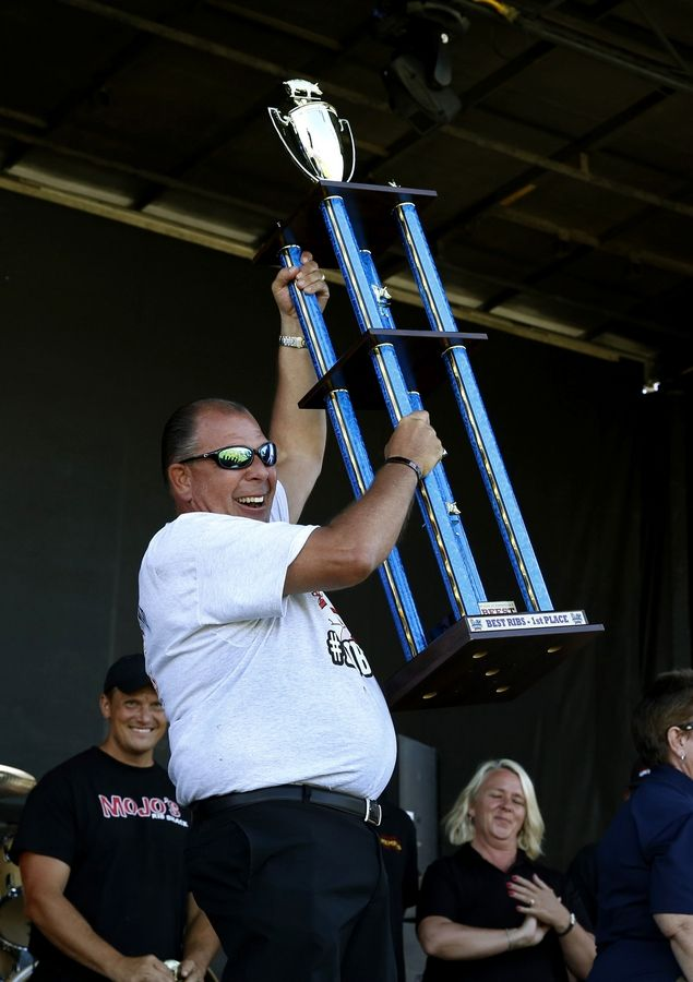 Mark Link of Uncle Bub's BBQ in Westmont celebrates winning the first place Best Ribs trophy Friday during the 31st annual Ribfest in Naperville.