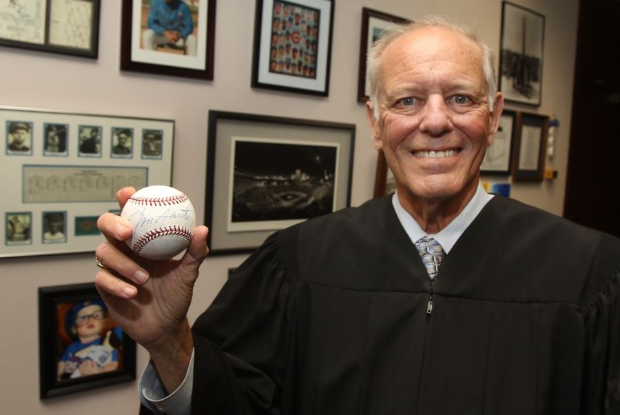Chicago Cubs fan and retiring Cook County Judge Hyman Riebman holds an autographed baseball signed by Ron Santo that he displays in his office.