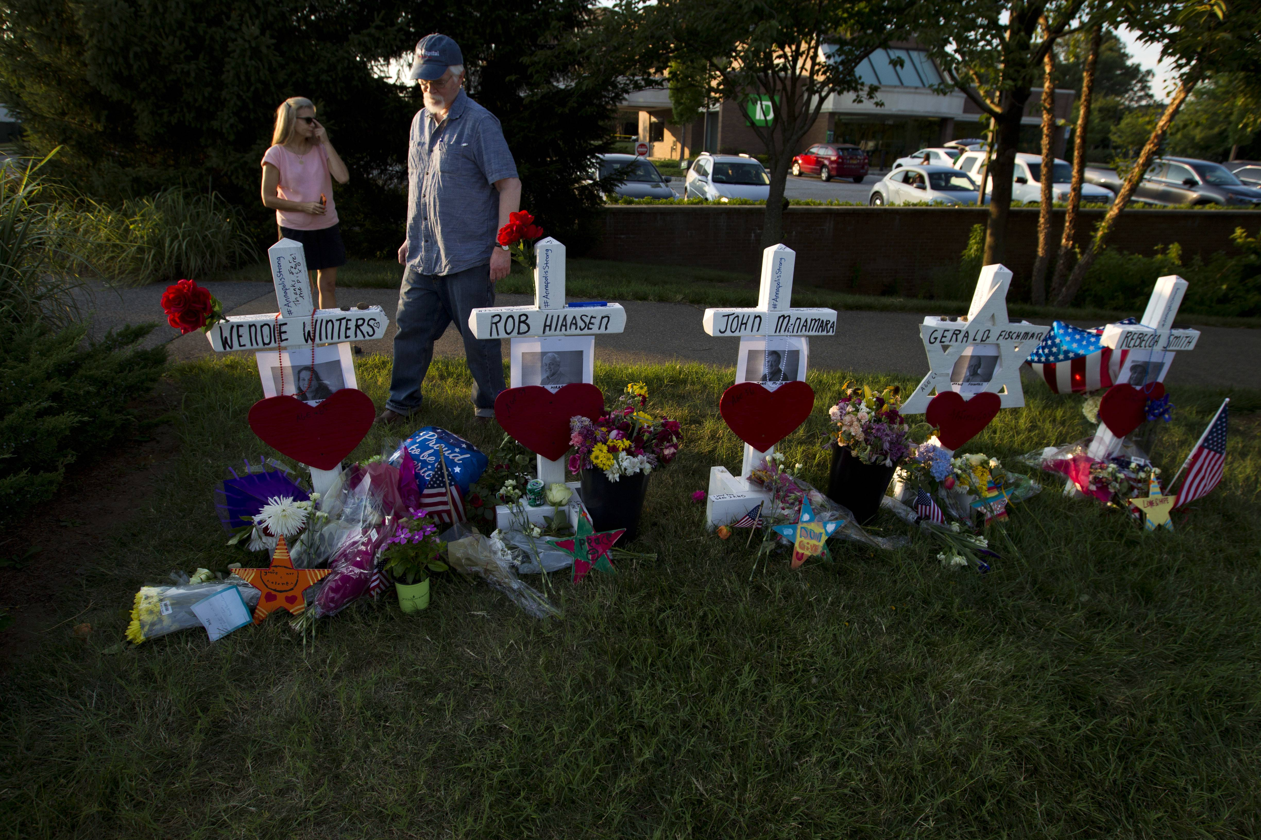 Capital Gazette reporter E.B. Furgurson III looks at crosses and a Star of David representing his five colleagues at a makeshift memorial outside the office building housing The Capital Gazette newspaper in Annapolis, Maryland.