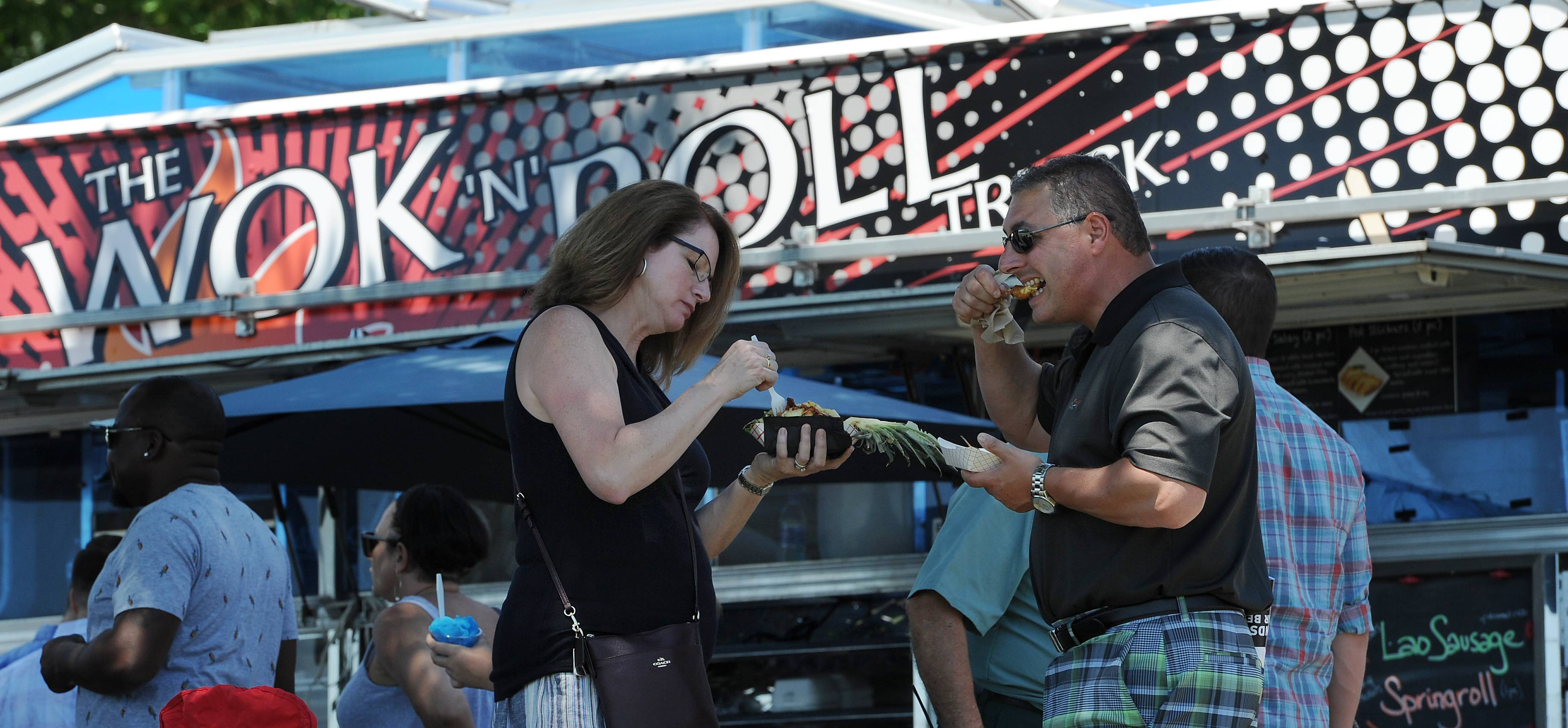Rocco and Darlene Morisco of Elgin sample the chicken and pineapple bowl as thousands of people turn out Saturday for the 5th annual Food Truck Festival at Arlington Park.