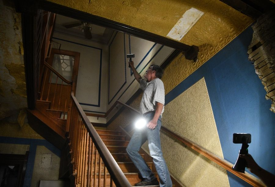 Dan Miller, president of the Gifford Park Association of Elgin, heads up the stairs of the David C. Cook mansion. The group hopes someone will restore the 1885 home to its old glory.
