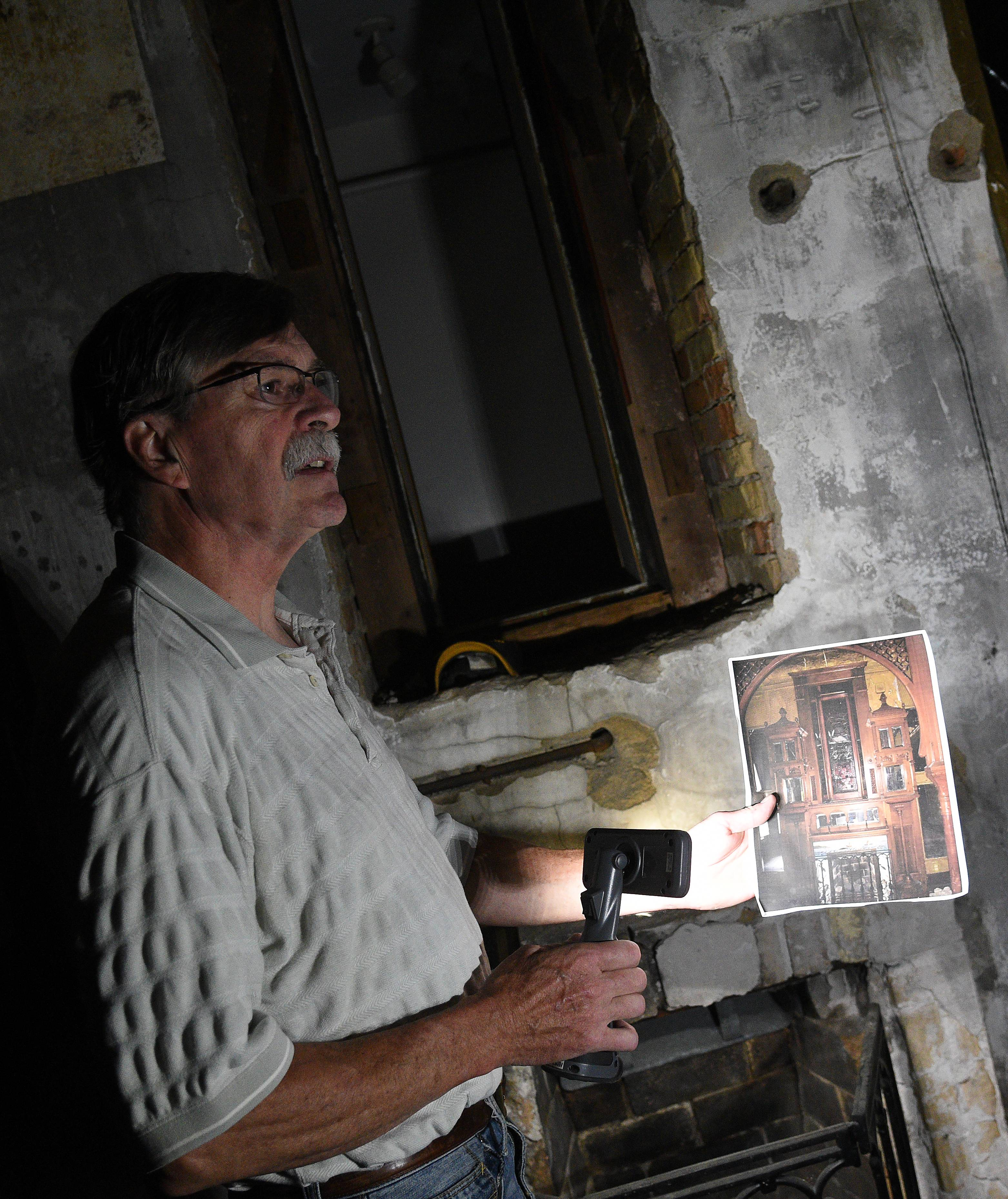 Dan Miller shows a photo of an ornate mantle that was removed by a salvage company at the historic David C. Cook mansion in Elgin.