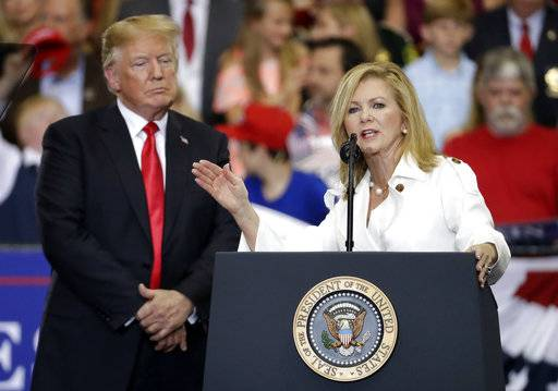 FILE - In this May 29, 2018, file photo, President Donald Trump listens as Rep. Marsha Blackburn, R-Tenn., speaks at a rally in Nashville, Tenn. The trade tension has re-shaped the race to replace retiring Republican Sen. Bob Corker in Tennessee, where Blackburn, has been one of the president's biggest boosters for the last two years. Yet with the local business community up in arms, she's dramatically softened her support, on Trump's trade policies, at least.