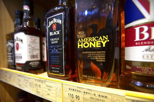 "Whiskeys distilled and bottled in the U.S. are displayed for sale in a grocery store in Beijing, Saturday, July 7, 2018. The trade war that erupted Friday between the U.S. and China carries a major risk of escalation that could weaken investment, depress spending, unsettle financial markets and slow the global economy. An executive at the Distilled Spirits Council said she fears China's tariffs on U.S. whiskey will ""put the brakes on an American success story"" of rising exports of U.S. spirits."