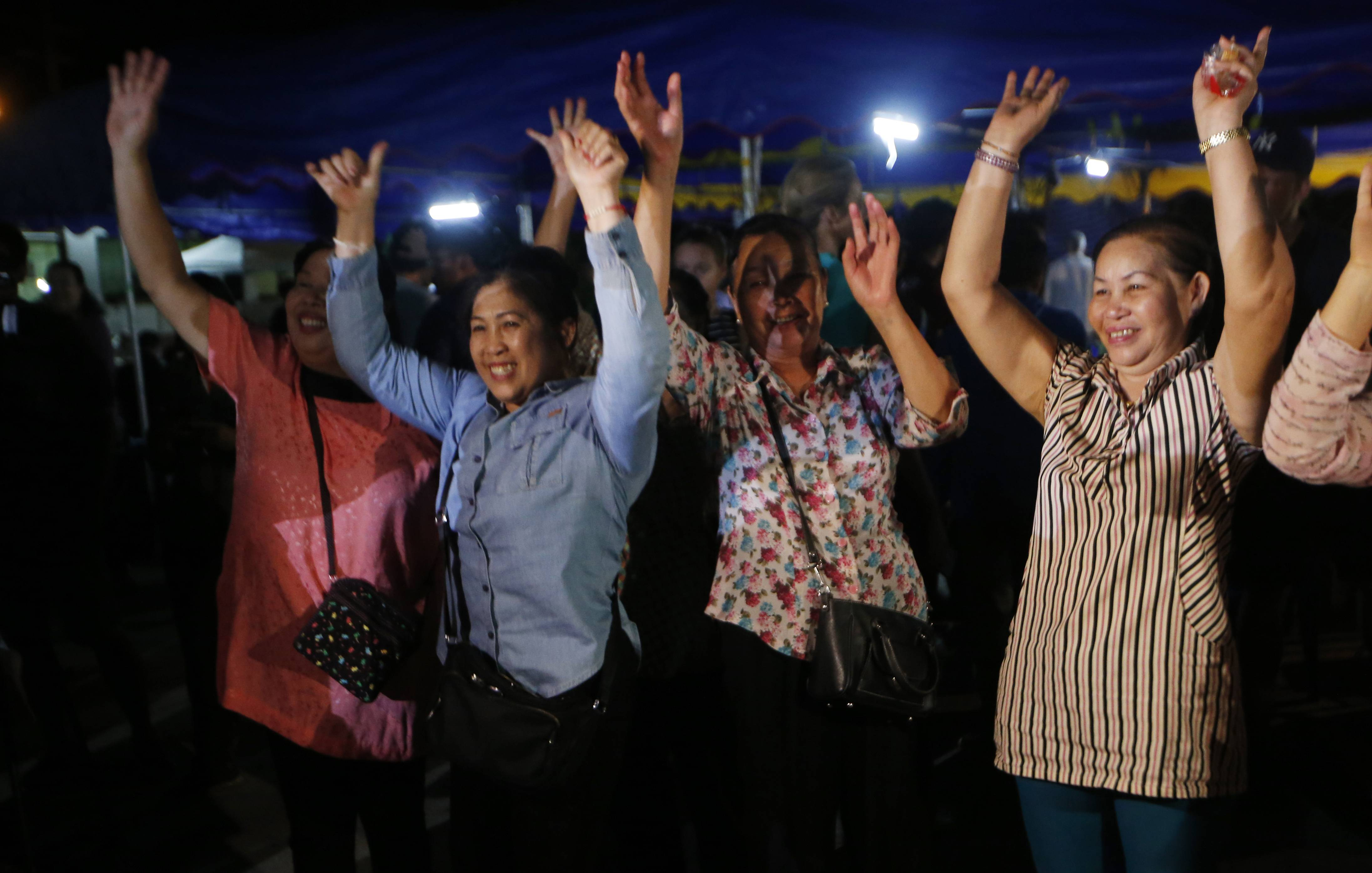 People celebrate Tuesday after divers rescued 12 boys and their coach trapped at Tham Luang cave in the Mae Sai district of Chiang Rai province, northern Thailand.