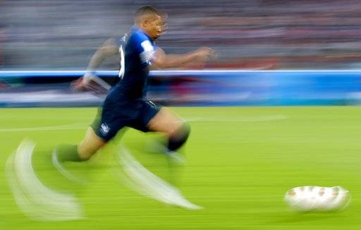 In this photo taken with slow shutter speed France's Kylian Mbappe runs with the ball during the semifinal match between France and Belgium at the 2018 soccer World Cup in the St. Petersburg Stadium, in St. Petersburg, Russia, Tuesday, July 10, 2018.
