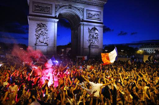 People celebrate on the Champs Elysees avenue, with the Arc de Triomphe in background, after the semifinal match between France and Belgium at the 2018 soccer World Cup, Tuesday, July 10, 2018 in Paris. France advanced to the World Cup final for the first time since 2006 with a 1-0 win over Belgium on Tuesday.