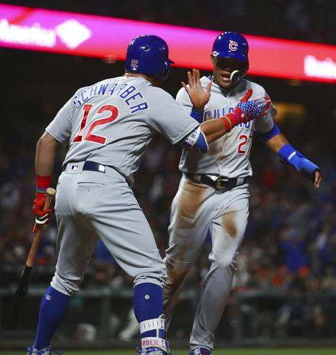Chicago Cubs' Addison Russell, right, is congratulated by Kyle Schwarber after scoring on a wild pitch, and throwing error by San Francisco Giants catcher Nick Hundley during the seventh inning of a baseball game Tuesday, July 10, 2018, in San Francisco.
