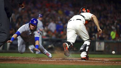 Chicago Cubs' Ian Happ, left, scores behind San Francisco Giants' Nick Hundley during the seventh inning of a baseball game Tuesday, July 10, 2018, in San Francisco.