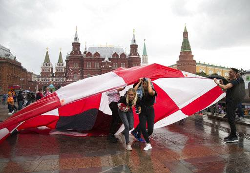 Soccer fans use a giant Croatian national flag as a shelter during the rain at Manezh Square near Red Square ahead of the semifinal soccer match between Croatia and England during the 2018 soccer World Cup at the Luzhniki stadium in Moscow, Russia, Wednesday, July 11, 2018.
