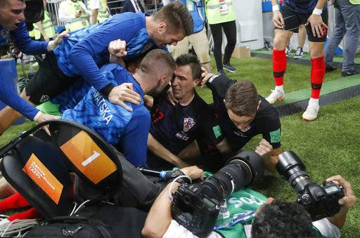 Croatia's Mario Mandzukic, sits on the ground after he fell over a photographer when celebrating his side's second goal during the semifinal match between Croatia and England at the 2018 soccer World Cup in the Luzhniki Stadium in Moscow, Russia, Wednesday, July 11, 2018.