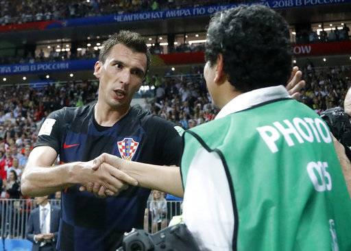 Croatia's Mario Mandzukic apologizes to a photographer he fell over when celebrating his side's second goal during the semifinal match between Croatia and England at the 2018 soccer World Cup in the Luzhniki Stadium in Moscow, Russia, Wednesday, July 11, 2018.