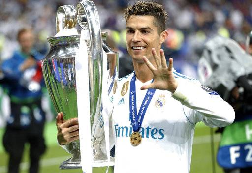 FILE - In this Saturday, May 26, 2018 file photo Real Madrid's Cristiano Ronaldo celebrates with the trophy after winning the Champions League Final soccer match between Real Madrid and Liverpool at the Olimpiyskiy Stadium in Kiev, Ukraine.