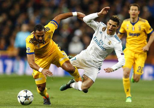 FILE - In this Wednesday, April 11, 2018 file photo Real Madrid's Cristiano Ronaldo is tackled by Juventus' Medhi Benatia during a Champions League quarter final second leg soccer match between Real Madrid and Juventus at the Santiago Bernabeu stadium in Madrid.